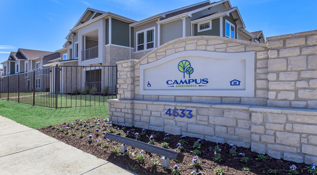 Two-story Campus Apartments building with apartment sign in the foreground