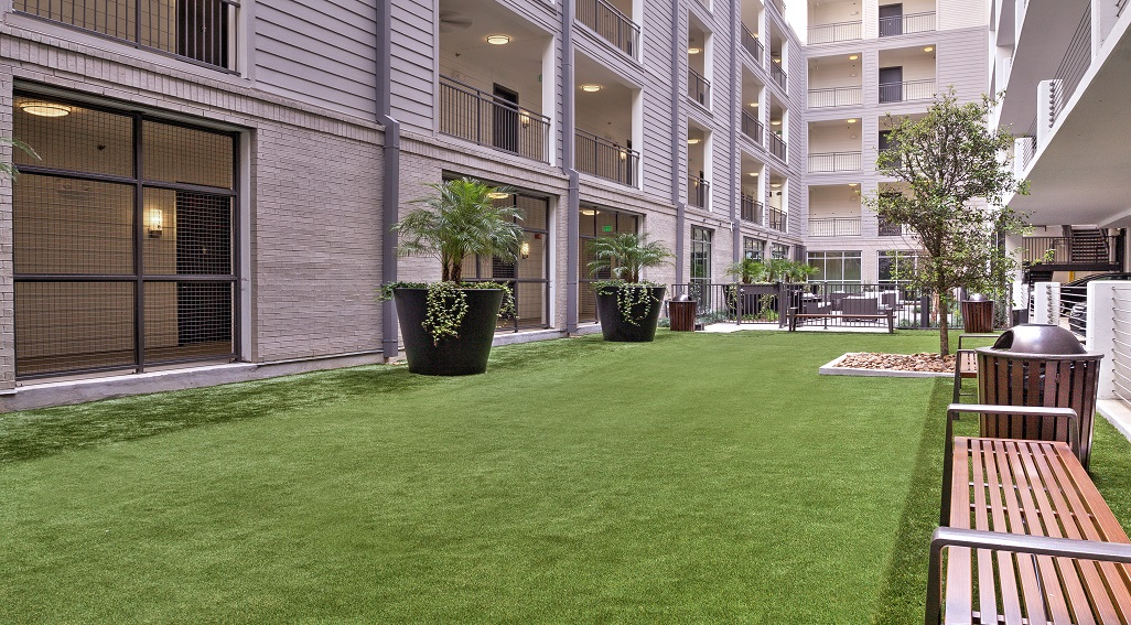 Outdoor patio with lawn and view of apartment balconies