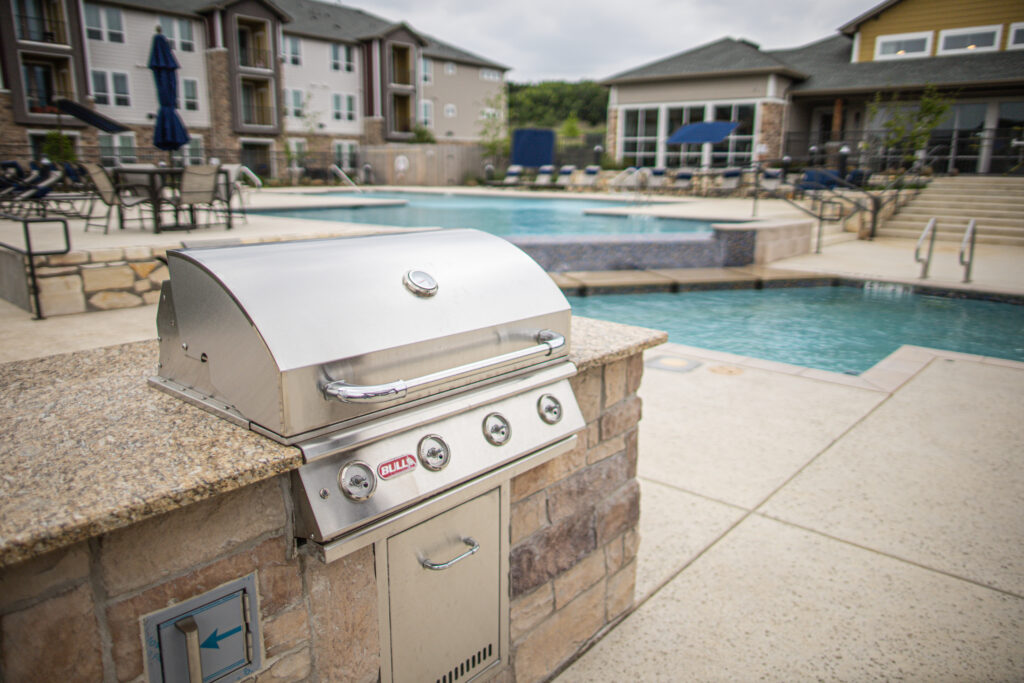 Detailed up-close view of BBQ in swimming pool area with apartment buildings in the background