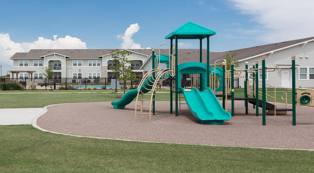 Avondale playground area with playground equipment including a blue slide.