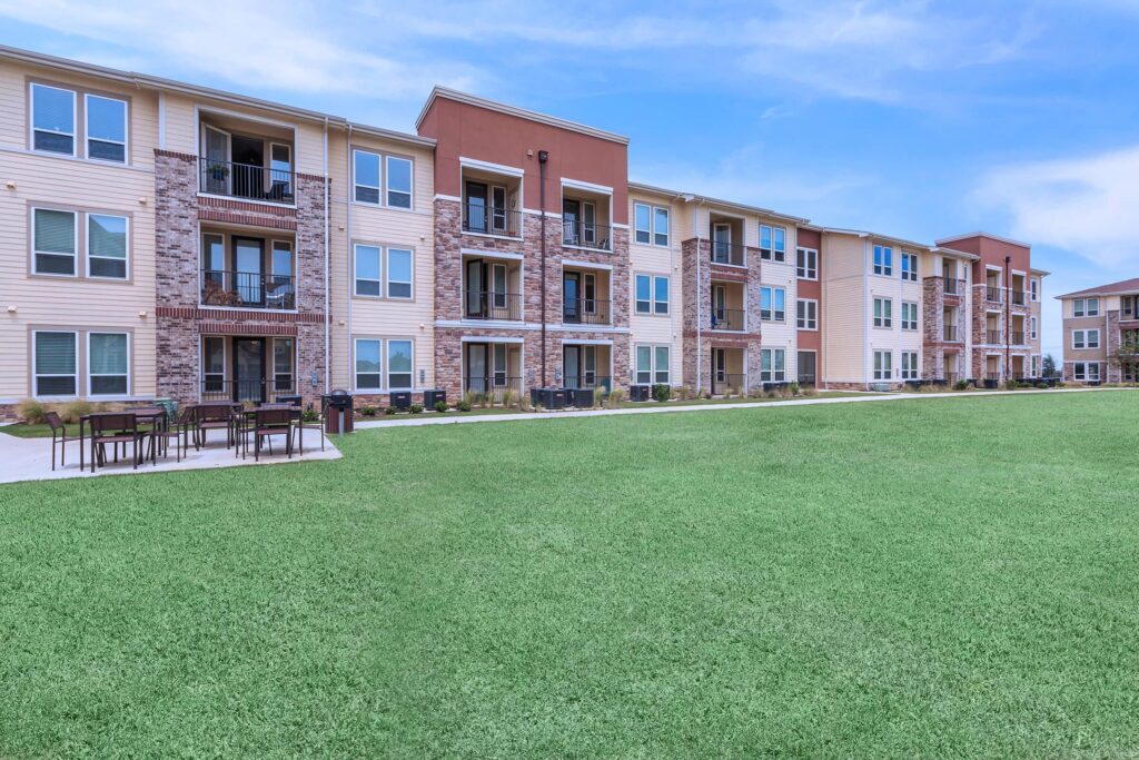 Three-story apartment building with brick and neutral brown facade. Green lawn in foreground.