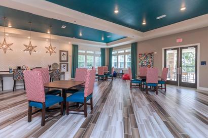 Parkdale clubhouse interior with three square tables and blue and red accent chairs.