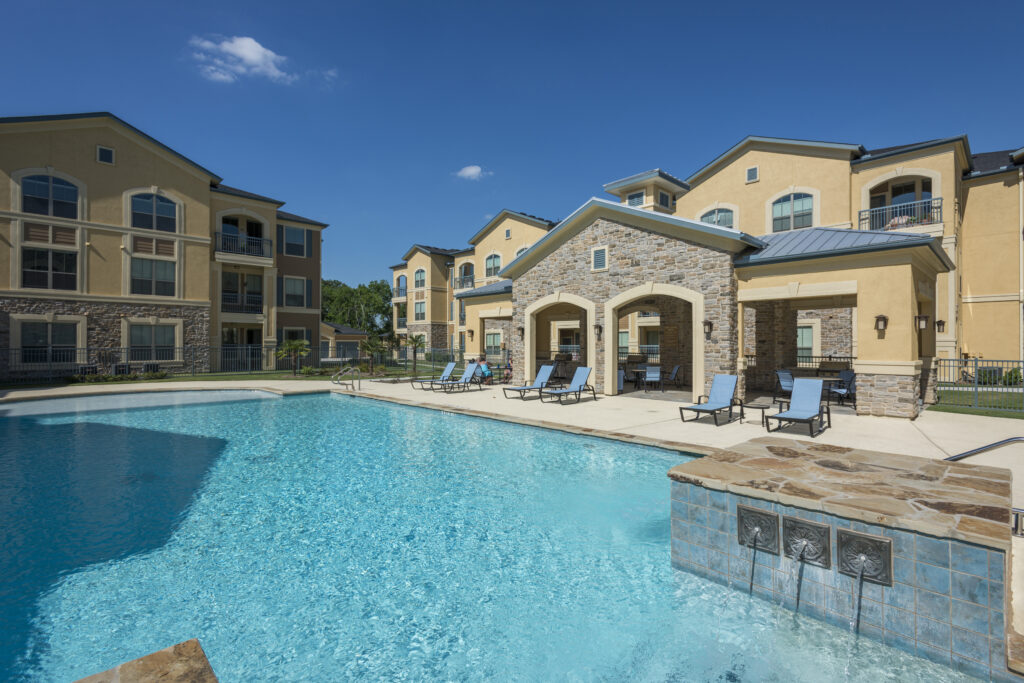 Photo of a swimming pool in front of a three-story multi-family apartment complex and clubhouse with stone facade.
